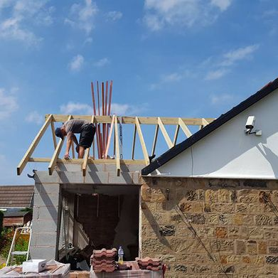 Work being done on a roof being added to an extension